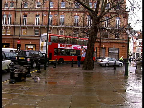London Sloane Square EXT General views around Sloane Square on grey cloudy day including shots of water fountain pigeons traffic London buses shops...