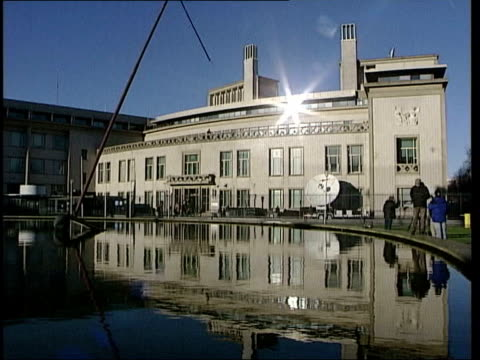 slobodan milosevic dies:; file / date unknown ext court building and fountain un flag flying outside court - slobodan milosevic stock-videos und b-roll-filmmaterial