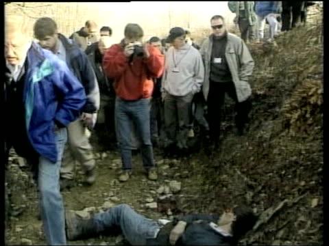 vídeos de stock, filmes e b-roll de slobodan milosevic handed over to war crimes tribunal lib racak war crimes investigators along to view bodies following massacre distressed woman... - sérvia