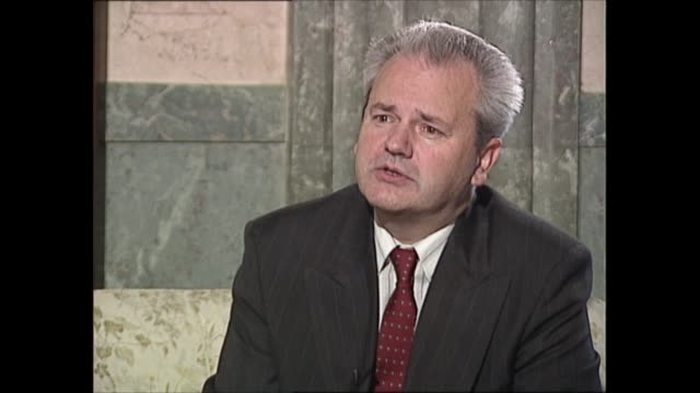 slobodan milosevic interview: part one; yugoslavia: serbia: belgrade: int gv doorway and slobodan milosevic along into room and shaking hands with... - slobodan milosevic stock-videos und b-roll-filmmaterial