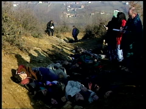 slobodan milosevic makes first court appearance; lib serbia: racak ext seq bodies of massacred muslims lying in ditch as people around - slobodan milosevic stock-videos und b-roll-filmmaterial