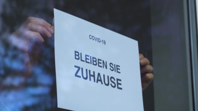bleiben sie zuhause slogan being placed in a window. - schild stock-videos und b-roll-filmmaterial