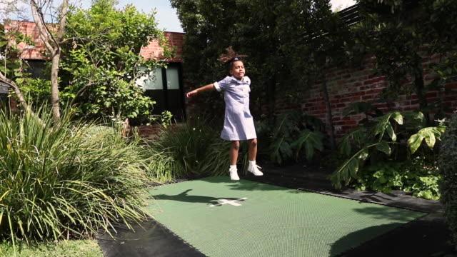 slom motion of jumping schoolgirl on trampoline - トランポリン点の映像素材/bロール