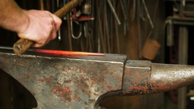 vídeos de stock e filmes b-roll de slomo blacksmith hitting glowing object on anvil - ferro metal
