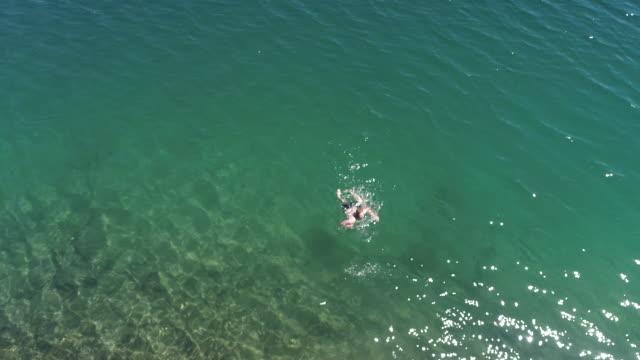 stockvideo's en b-roll-footage met kaukasische man slomo zwemmen in het kristalheldere water - fatcamera