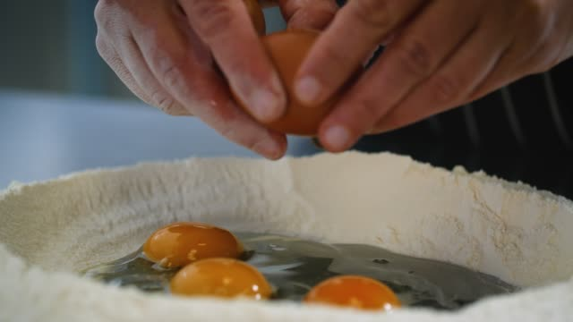 slomo eggs cracked into mound of flour - egg stock videos & royalty-free footage