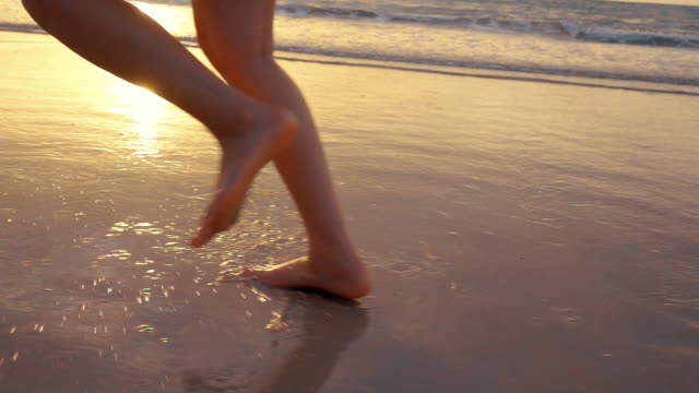 slomo: menschliche beine am strand - variable schärfentiefe stock-videos und b-roll-filmmaterial