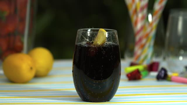 vidéos et rushes de slomo lemon wedge falls into glass of cola - part of a series