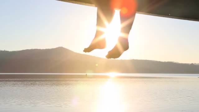 Slo-mo of woman's feet dangling over edge of pier toward lake