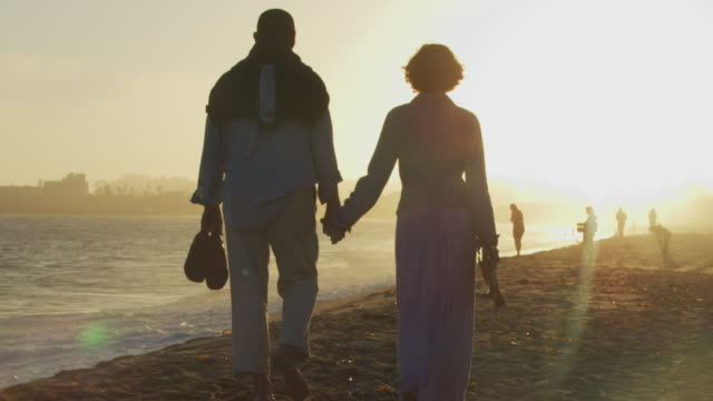 SloMo WS Older couple walking on beach at sunset