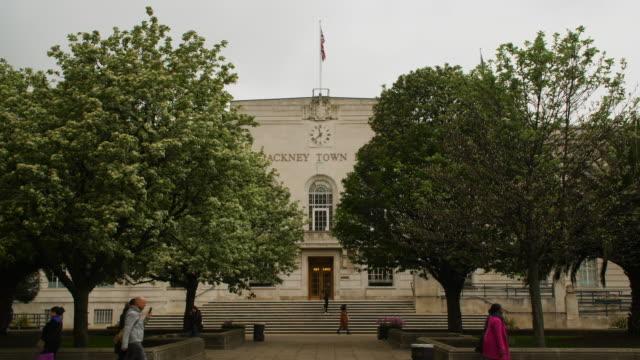 slomo pedestrians and traffic pass hackney town hall, london - rathaus stock-videos und b-roll-filmmaterial