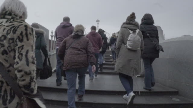 slo-mo people, commuters walk over river footbridge to work, europe / ireland / dublin - large group of animals点の映像素材/bロール