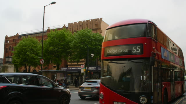 slomo red bus and traffic passes hackney empire, london - double decker bus stock videos & royalty-free footage