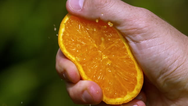 slomo speed ramp hand squeezing orange - orange colour stock videos & royalty-free footage