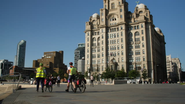 slomo tilt down to skateboarders in front of royal liver building - reflective clothing stock videos & royalty-free footage