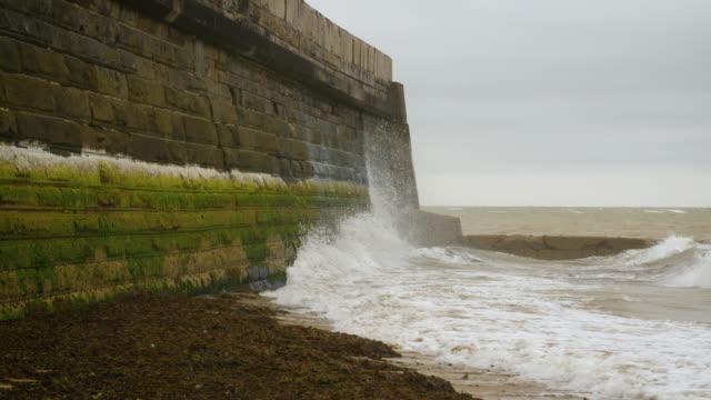 slomo waves crash against sea wall - coastal feature stock videos & royalty-free footage