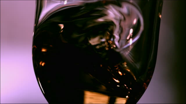 cu slomo whisky swirled in glass - alcohol abuse stock videos & royalty-free footage