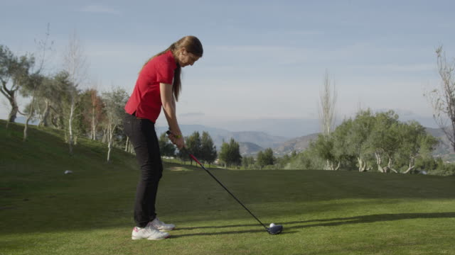 MS slo-mo young female golfer teeing off, rear view, RED R3D 4K