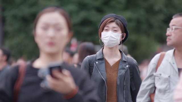 slomo young people walking in tokyo - pollution mask stock videos & royalty-free footage