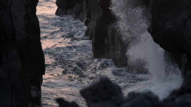 slomos water dramatically crashes between rocks - philippine sea stock videos & royalty-free footage