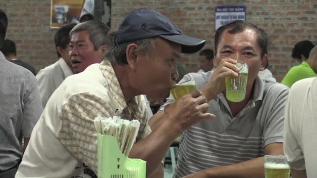 sloshed back at rowdy open air bia hoi day and night beer is vietnam's tipple of choice and now its cash strapped government is drawing on the... - lager stock videos & royalty-free footage