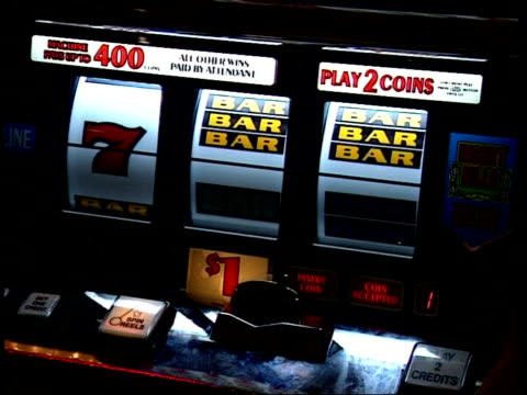 CU slot machine/fruit machine being played, hand puts money in and pulls lever, Las Vegas