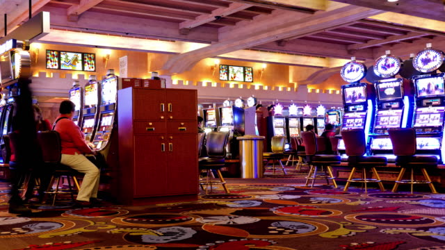 stockvideo's en b-roll-footage met t/l zi slot machines in gambling casino with empty chairs  / las vegas, nevada, usa  - casino