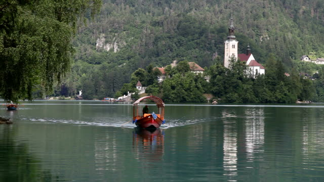 slovenia, bled, rowboat crossing lake bled - lago di bled video stock e b–roll