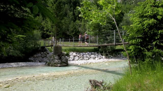 Slovenia, Bovec, Trenta valley, women crossing the Soca river on a suspension bridge