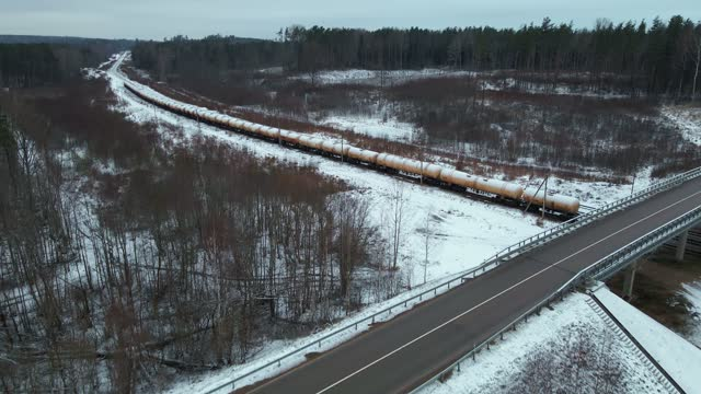 slow aerial flight over bridge revealing stationary cistern tank train covered in snow during winter - stationary stock-videos und b-roll-filmmaterial