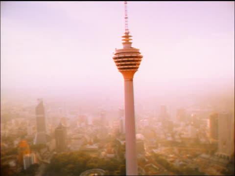 slow aerial observation tower / sun in background / kuala lumpur, malaysia - メナラクアラルンプールタワー点の映像素材/bロール