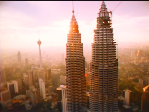 slow aerial petronas twin towers / sun in background / kuala lumpur, malaysia - petronas twin towers stock-videos und b-roll-filmmaterial