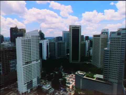 vídeos de stock e filmes b-roll de slow aerial point of view petronas twin towers + skyscrapers / kuala lumpur - edifício do sultão abdul samad