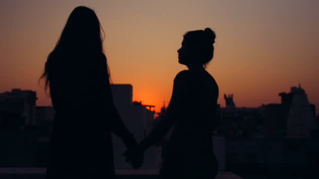 slow angle silhouette view of two women holding hands together in romantic sunset setting as they hold hands embrace hug share flirt on date proposal viewpoint - lesbian stock videos & royalty-free footage