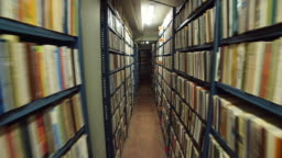 Slow camera movement between two archive shelves filled with folders