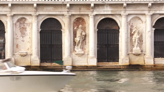 slow camera zoom in on distressed statues in venice, italy while boats in the canal pass by in the foreground on september 2, 2018. - distressed video stock e b–roll