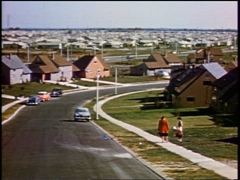 vidéos et rushes de 1956 slow car point of view on suburban street with houses + two people on sidewalk / levittown, pa - 1956
