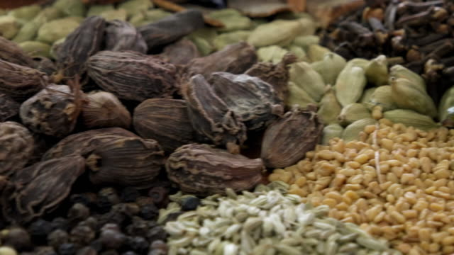 A slow close-up tracking shot through various Indian spices and masalas