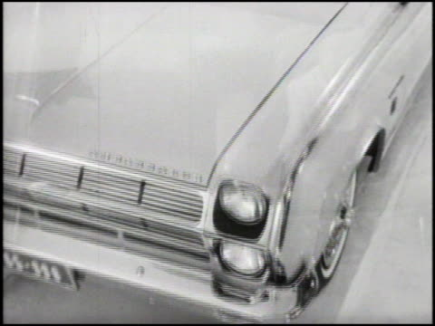 WS slow DOLLY IN to blond sitting in a 1965 AMC Ambassador 990 convertible in a white studio / DISSOLVE TO WS front end of car DOLLY IN as camera...