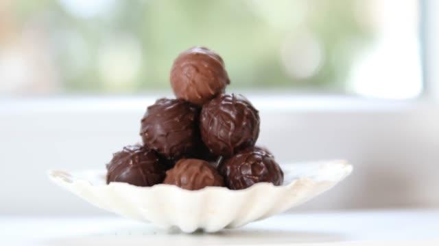vídeos y material grabado en eventos de stock de slow dolly move across chocolates in a flat bowl - dulces