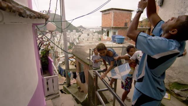 vídeos de stock e filmes b-roll de rio de janeiro, brazil - june 23: slow dolly shot, favela occupants on jun 23, 2013 in rio, brazil - favela