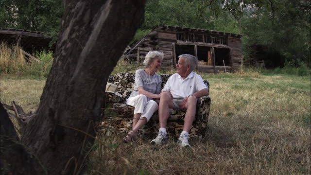 Slow dolly shot of an affectionate old couple having a conversation on a couch outdoors