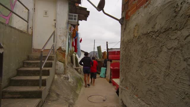 Slow dolly shot of kids walking in a favela on June 23, 2013 in Rio de Janeiro, Brazil