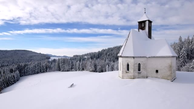 slow drone flight besides a snowy mountain catholic church - 40 sekunden oder länger stock-videos und b-roll-filmmaterial