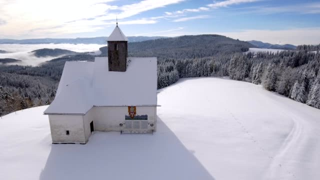 Slow drone flight besides a snowy mountain catholic church