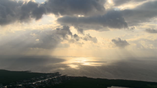 slow flight along florida coastline near miami, evening rays gleaming on water - artbeats 個影片檔及 b 捲影像