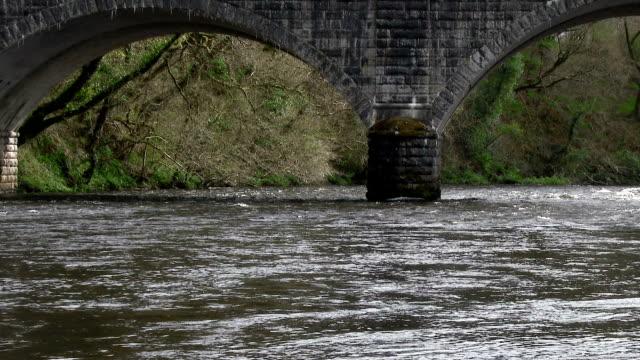 Lente rivière en passant sous le pont de pierre