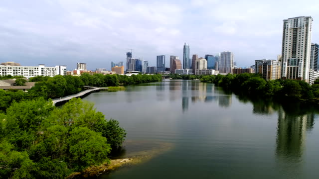 vídeos de stock e filmes b-roll de slow forward aerial drone view austin texas downtown reflections of glass like water on town lake - town