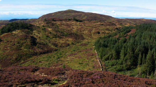 slow forward dolly shot captured by a drone as it is flown over a cairn on a scottish hilltop - johnfscott stock videos & royalty-free footage