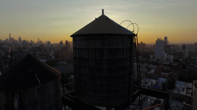 vídeos de stock, filmes e b-roll de slow glide down behind water towers in soho, new york city at sunrise - inclinação para baixo
